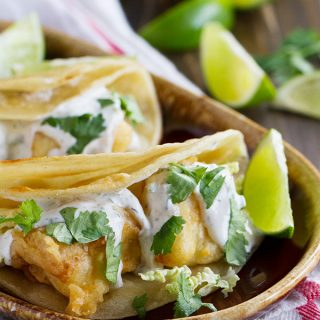 A taste of San Diego, these fried fish tacos have pieces of battered, fried fish inside corn tortillas, topped with a creamy, tangy white sauce.