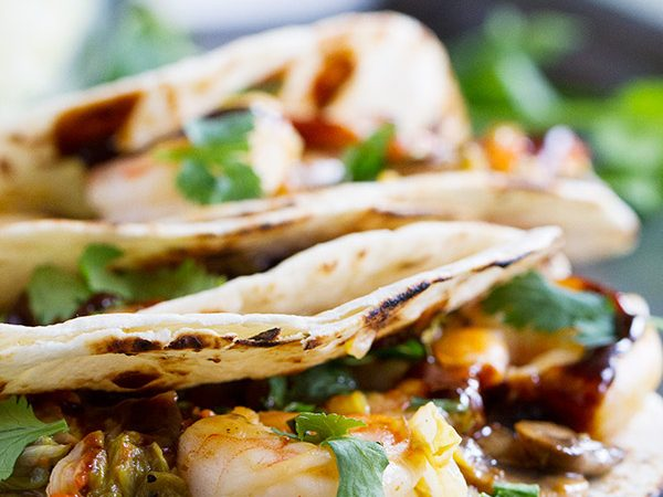 Tacos go Asian in this easy weeknight meal. These Moo Shu Shrimp tacos have shrimp combined with mushrooms, carrots, green onions and cabbage and a simple sauce. The mixture is served in tortillas, topped with hoisin sauce and cilantro.