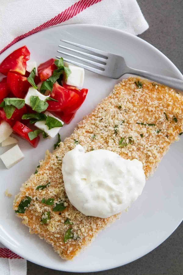 This Crispy Baked Salmon is super easy and can be on your table in less than 30 minutes. Topped with an easy homemade tartar sauce, this salmon can't be beat!