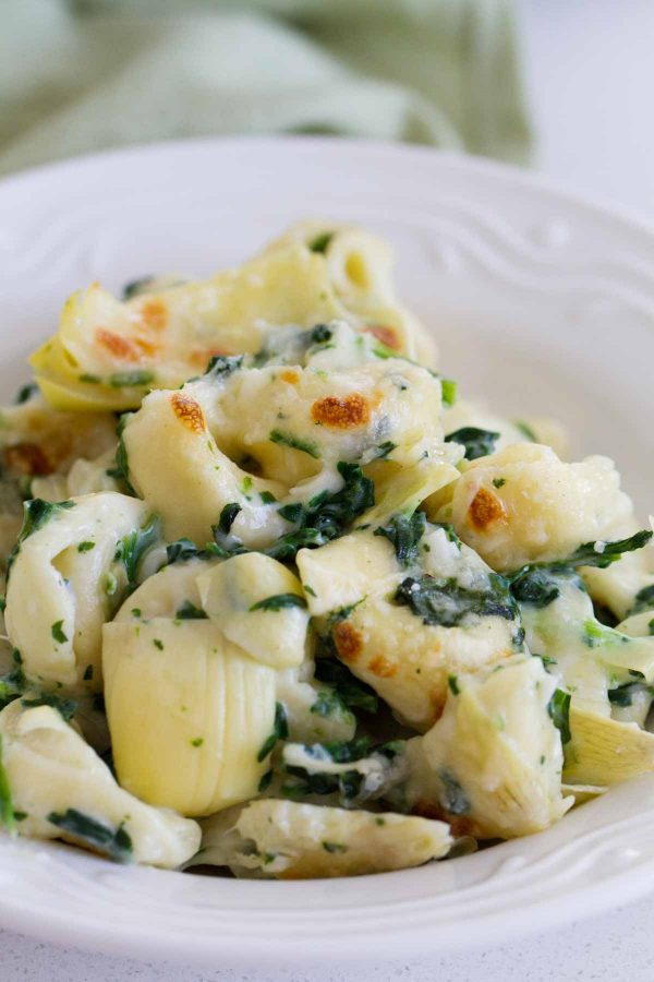 Everyone's favorite dip gets a makeover - into an easy family dinner! This Spinach and Artichoke Tortellini Bake is cheesy, creamy and super easy!