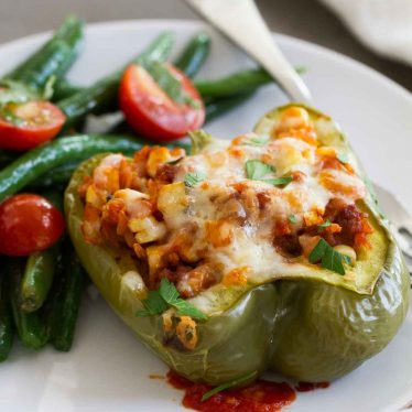 The perfect way to get in your veggies, these Vegetable and Sausage Stuffed Peppers are stuffed with lots of veggies, rice and flavorful sausage. The perfect end of summer meal!