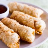 homemade egg rolls on a plate with sweet and sour sauce