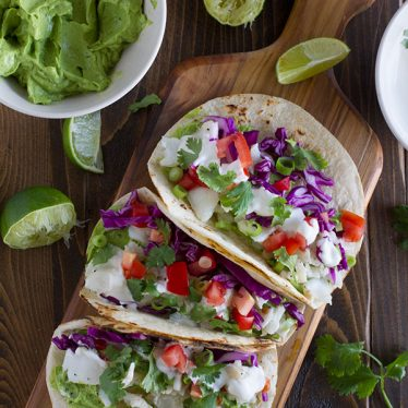 A healthier fish taco, this Baja Fish Taco Recipe has grilled flaky white fish, a creamy avocado sauce, and a tangy white mayo sauce. My idea of a perfect taco night!