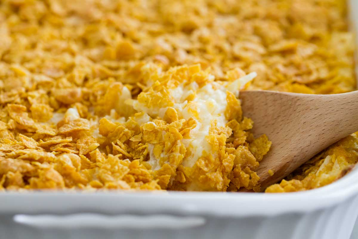 dish of funeral potatoes with wooden spoon