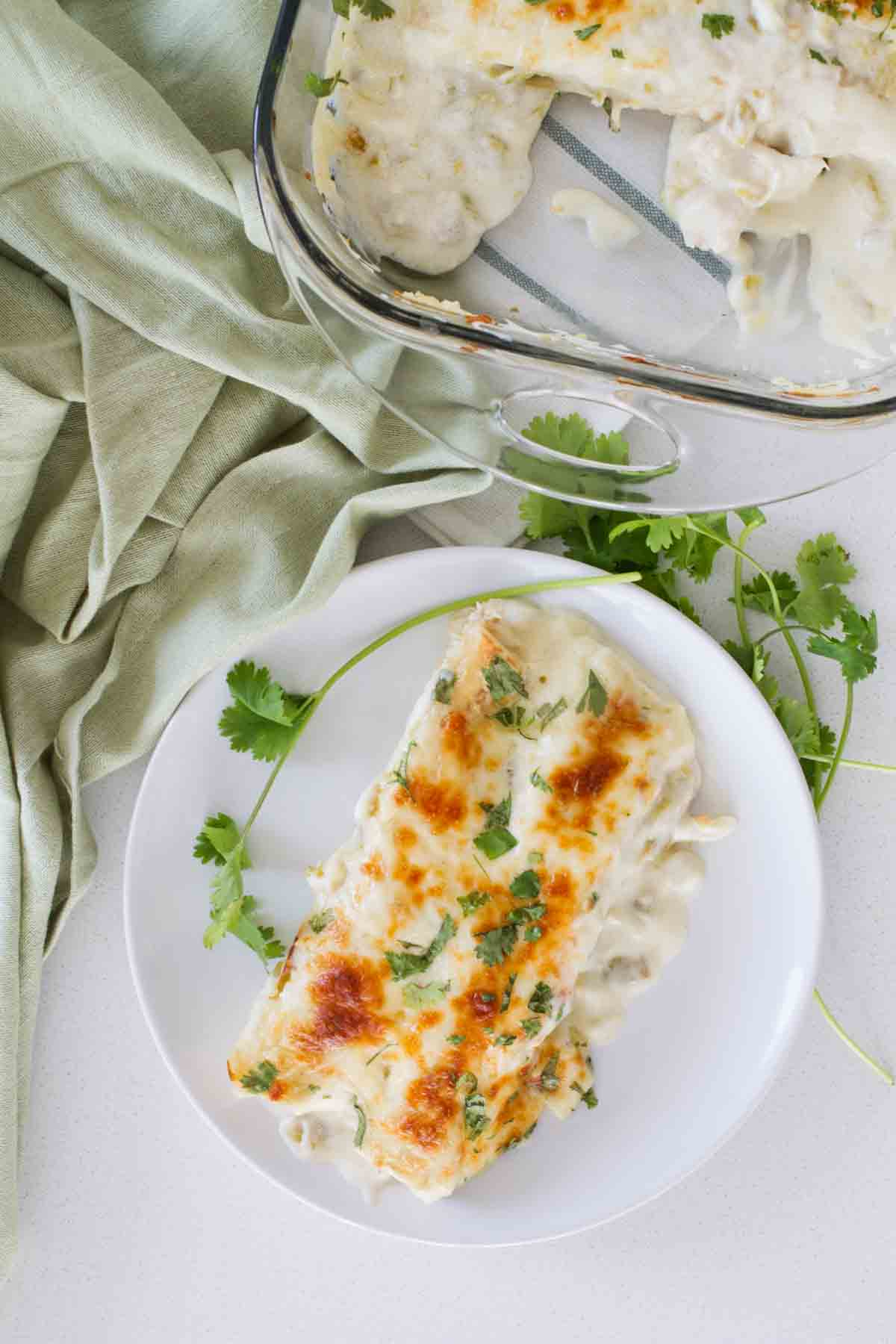 chicken enchiladas on a plate with cilantro