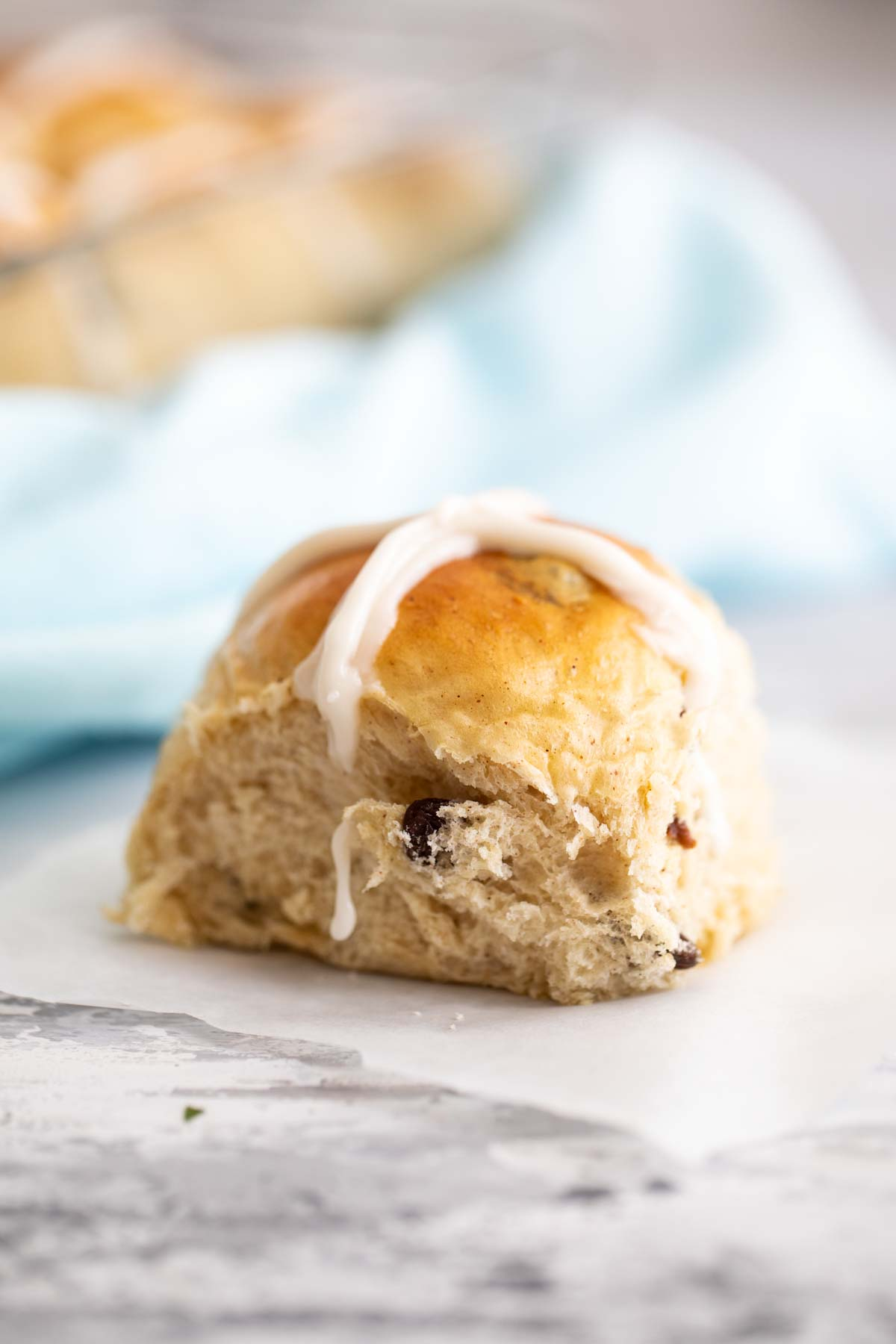 single hot cross bun on parchment paper