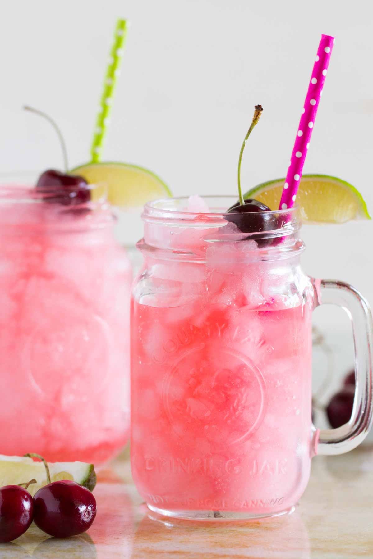 homemade slurpees in glasses with lime slices, cherries and straws