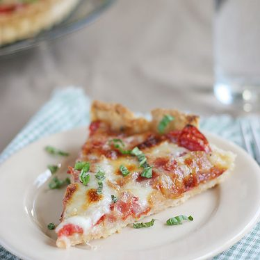 A buttery, flaky crust is filled with fresh tomatoes, bacon and lots of cheese for the perfect end of summer Tomato Tart Recipe.