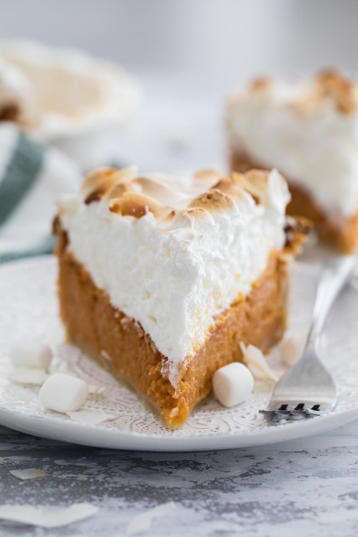 slice of sweet potato pie with tall meringue on a plate with a fork
