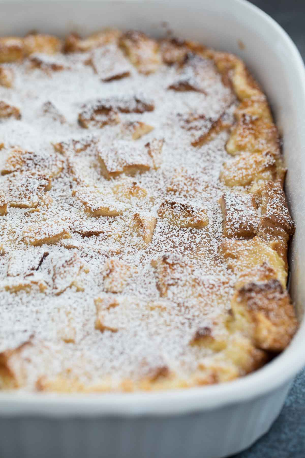 casserole dish with French Toast Casserole sprinkled with powdered sugar