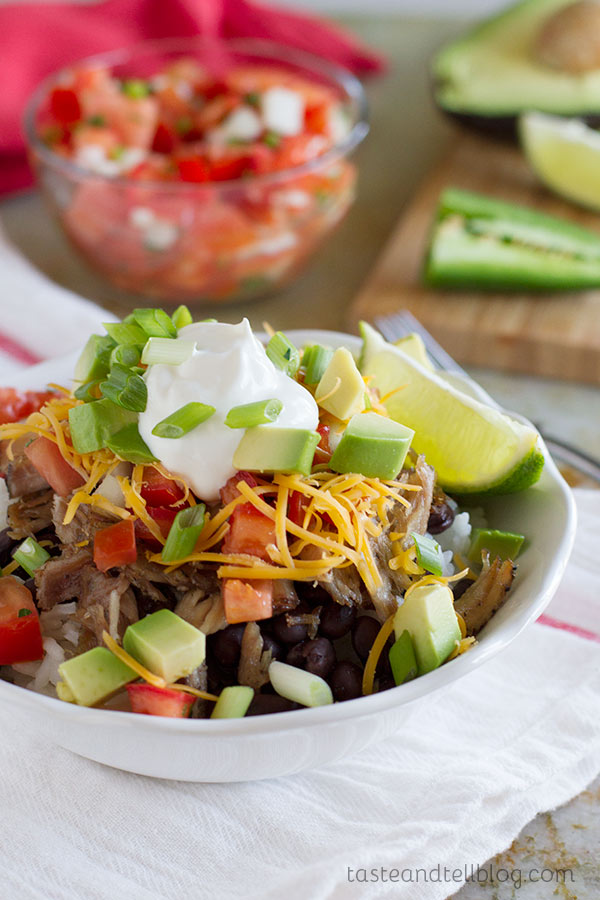 Caramelized pork carnitas are served over beans and rice, and topped with a fresh pico de gallo to make a burrito bowl that will rival the local take out joint!