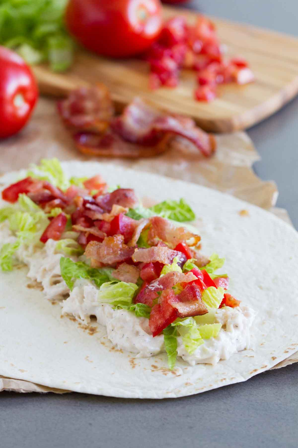 adding ingredients to tortilla for a chicken wrap