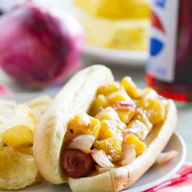 Take a taste of the tropics with these Hawaiian Hot Dogs - grilled hot dogs topped with grilled fresh pineapple and onions for a Hawaiian flair.