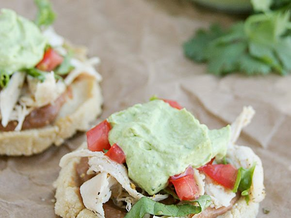 These Chicken Sopes are made from fried corn masa harina that is raised on the sides, then filled with chicken, beans, lettuce and tomatoes and then finished off with an avocado cream.