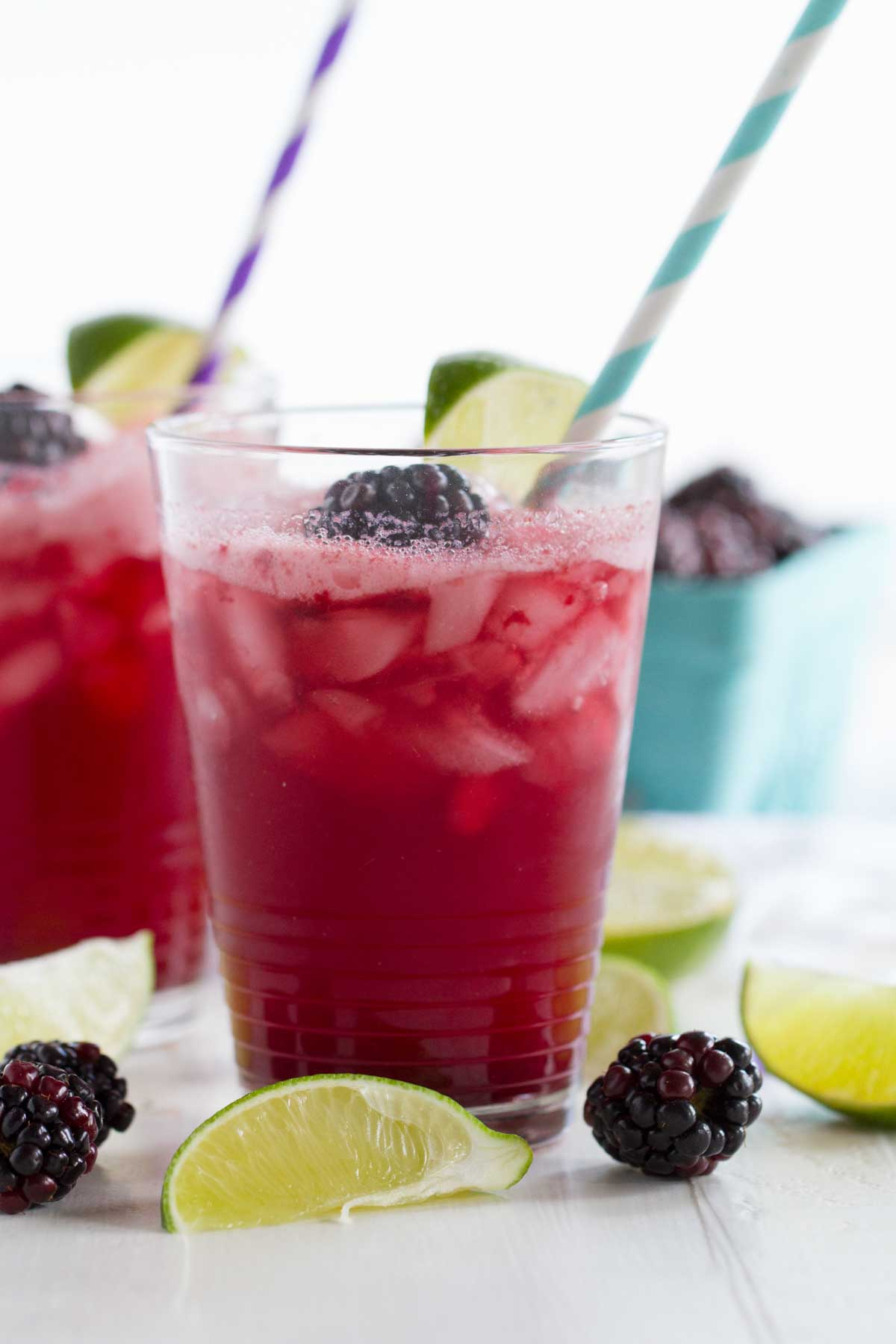 glasses with blackberry lime soda with lime slices and blackberries around
