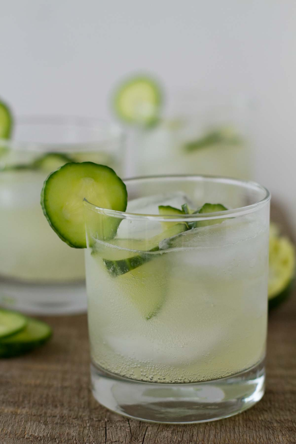 cucumber limeade in a glass with ice and cucumbers