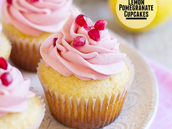 Lemon cupcakes are topped with a light pomegranate frosting and fresh pomegranate seeds in these light and refreshing Lemon Pomegranate Cupcakes.