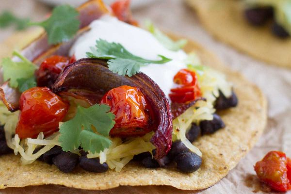 These vegetarian Spaghetti Squash Tostadas are filled with roasted tomatoes and onions, spaghetti squash, and black beans.