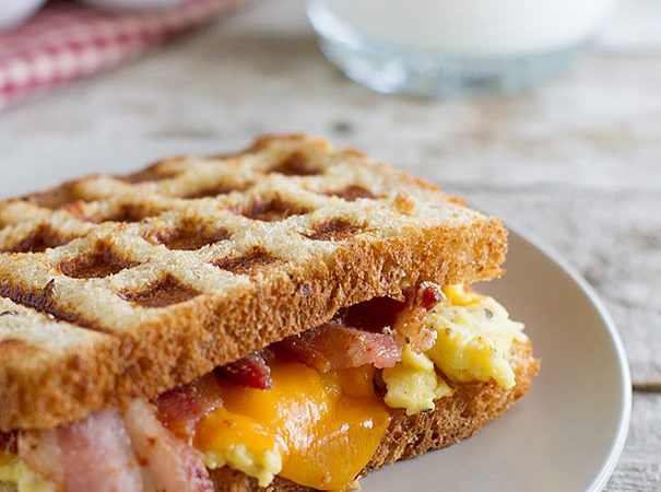 Waffled Breakfast Grilled Cheese Sandwich Recipe - Grilled cheese breakfast style! A breakfast grilled cheese sandwich recipe has scrambled eggs, bacon and cheese on toast that is cooked in a waffle maker for a fun breakfast idea.