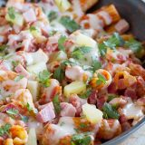 Keep dishes to a minimum with this easy one pan pasta with the flavors of a Hawaiian pizza - ham, bacon, pineapple and gooey cheese.