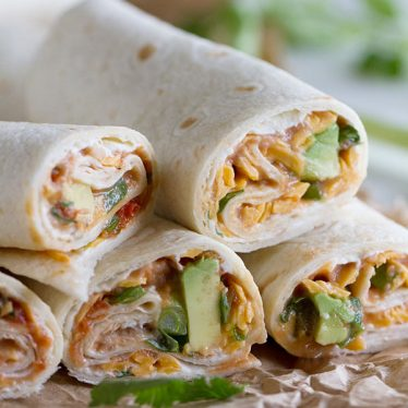 These Vegetarian Wraps with Beans and Cheese make the perfect grab and go lunch. Filled with cream cheese, refried beans, cheese, salsa, green onions, cilantro and avocado, they will make your taste buds will be happy!