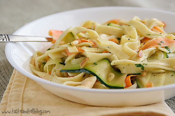 Egg noodles are served with ribbons of carrots and zucchini in a light cream sauce.