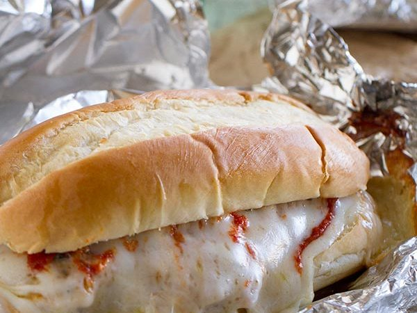 Chicken Parmesan goes sandwich style in these easy and portable Oven Baked Chicken Parmesan Sandwiches. Breaded chicken is topped with marinara, cheese and basil, layered on a roll, then baked in a foil packet.
