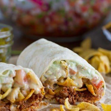 The ultimate Tex-Mex burrito - this Frito Pie Burrito is filled with chili, green chile queso, pico de gallo, avocado cream and jalapenos, all wrapped up in a tortilla.