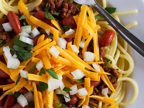 Beef chili is served over spaghetti and topped with beans, cheese and onion in this traditional Cincinnati Chili Recipe.