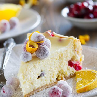 This Cranberry Orange Cheesecake is a showstopper - an orange scented cheesecake is filled with fresh cranberries, then topped with sweet sugared cranberries. It is so creamy and delicious - no one will believe that it's homemade!