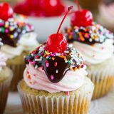 Banana splits - minus the ice cream! These Banana Split Cupcakes have tender, fluffy banana cupcakes topped with vanilla and strawberry frosting. Top it off with chocolate ganache, sprinkles and a cherry for the cupcake version of a banana split!