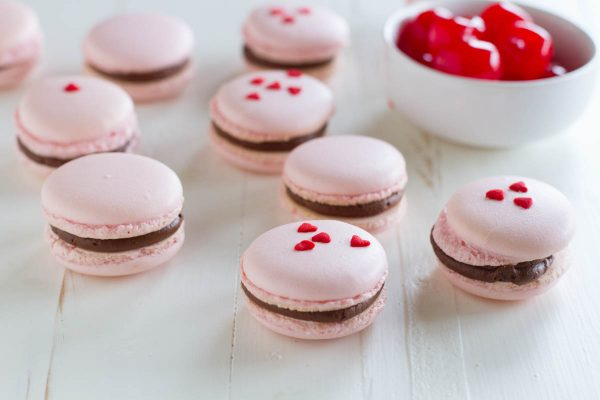 French macarons, made using the Italian Meringue Method, are filled with a chocolate buttercream and a maraschino cherry. These chocolate cherry French Macarons are the perfect way to jazz up a chocolate covered cherry!