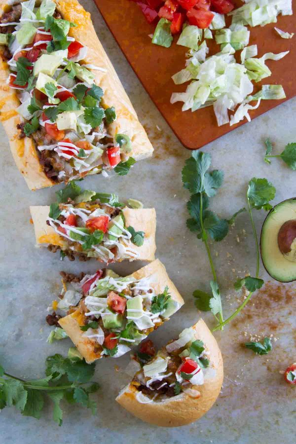 Taco Tuesday looks a little different with this Taco French Bread Pizza taking center stage! All of your favorite taco flavors are nested in a loaf of French bread for a dinner the whole family loves.