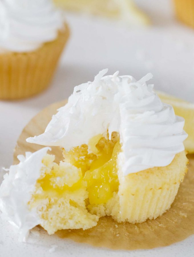 Bring in a little bit of sunshine with these Lemon Sunshine Cupcakes! Based on an old favorite cake, these cupcakes are filled with lemon curd and topped with a dreamy fluffy frosting. A sprinkling of coconut tops them off.