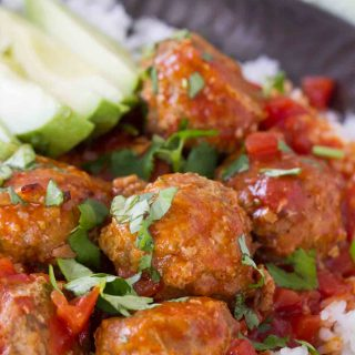 Taco spiced meatballs are slow cooked in an easy enchilada sauce. Serve the over rice or tortilla chips or turn them into a Tex-Mex style hoagie sandwich!