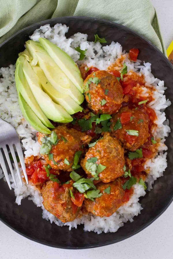 Taco spiced meatballs are slow cooked in an easy enchilada sauce. Serve these Tex-Mex Slow Cooker Meatballs over rice or tortilla chips or turn them into a Tex-Mex style hoagie sandwich!