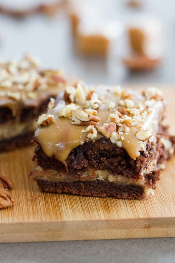 Forget the fancy bakery - these Turtle Cheesecake Cookie Bars are an impressive dessert you can make at home! A chocolate cookie base, a caramel cheesecake center, and lots of chocolate, caramel and pecans to top them off!