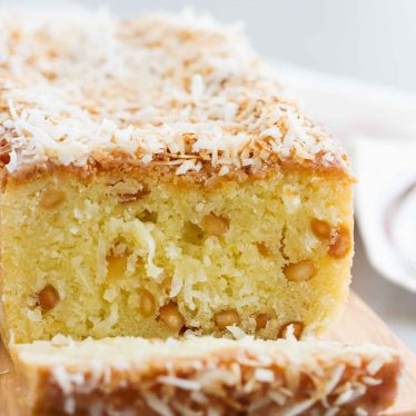 Transport yourself to the tropics with this Kona Coconut Loaf! Sweet pineapple and nutty macadamia nuts make this loaf cake the perfect dessert for when you are wanting something tropical.