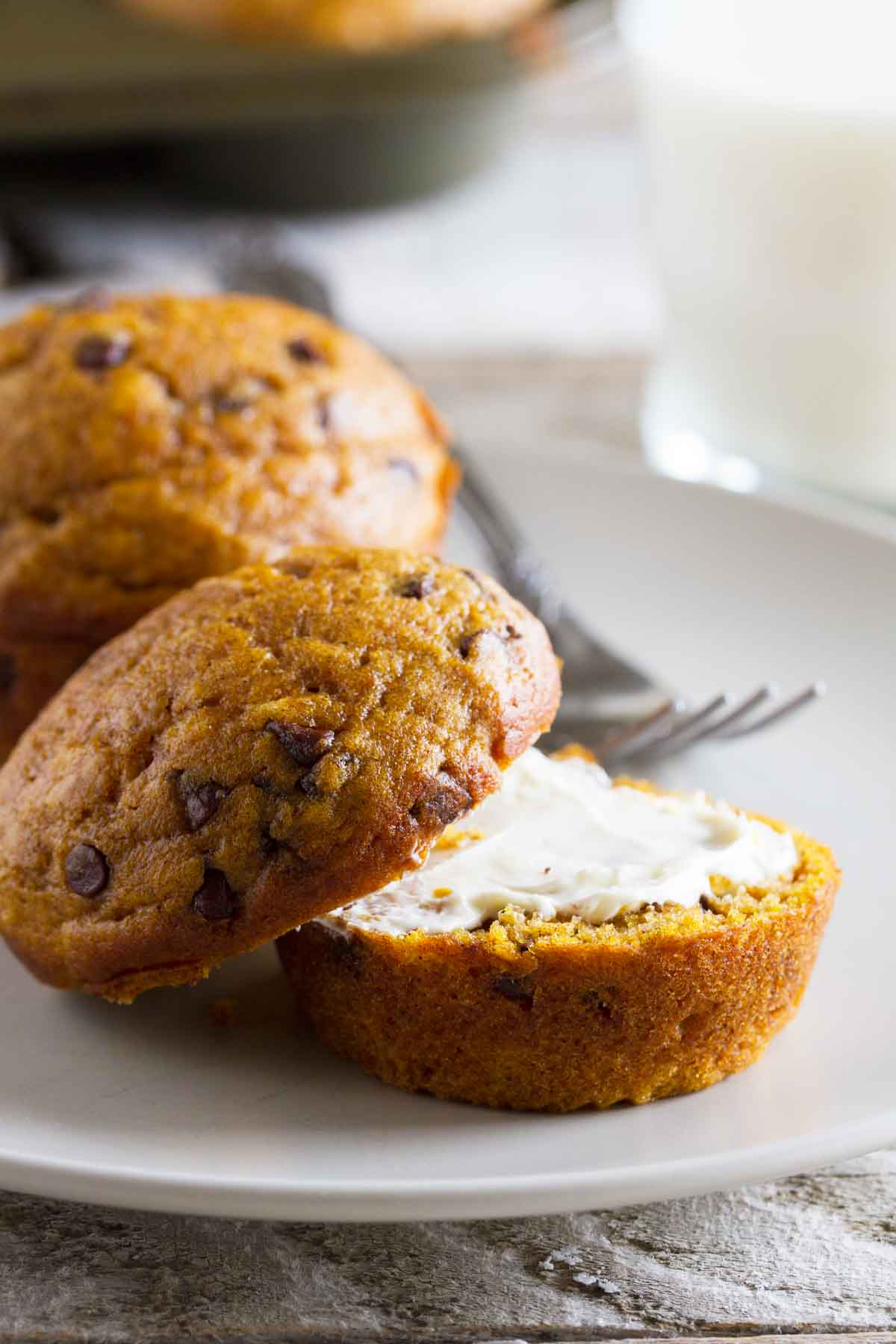 Pumpkin Chocolate Chip Muffin on a plate cut open with butter