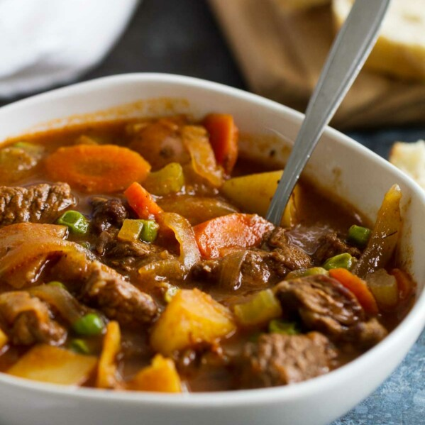 Bowl of Homemade Beef Stew with bread in the background