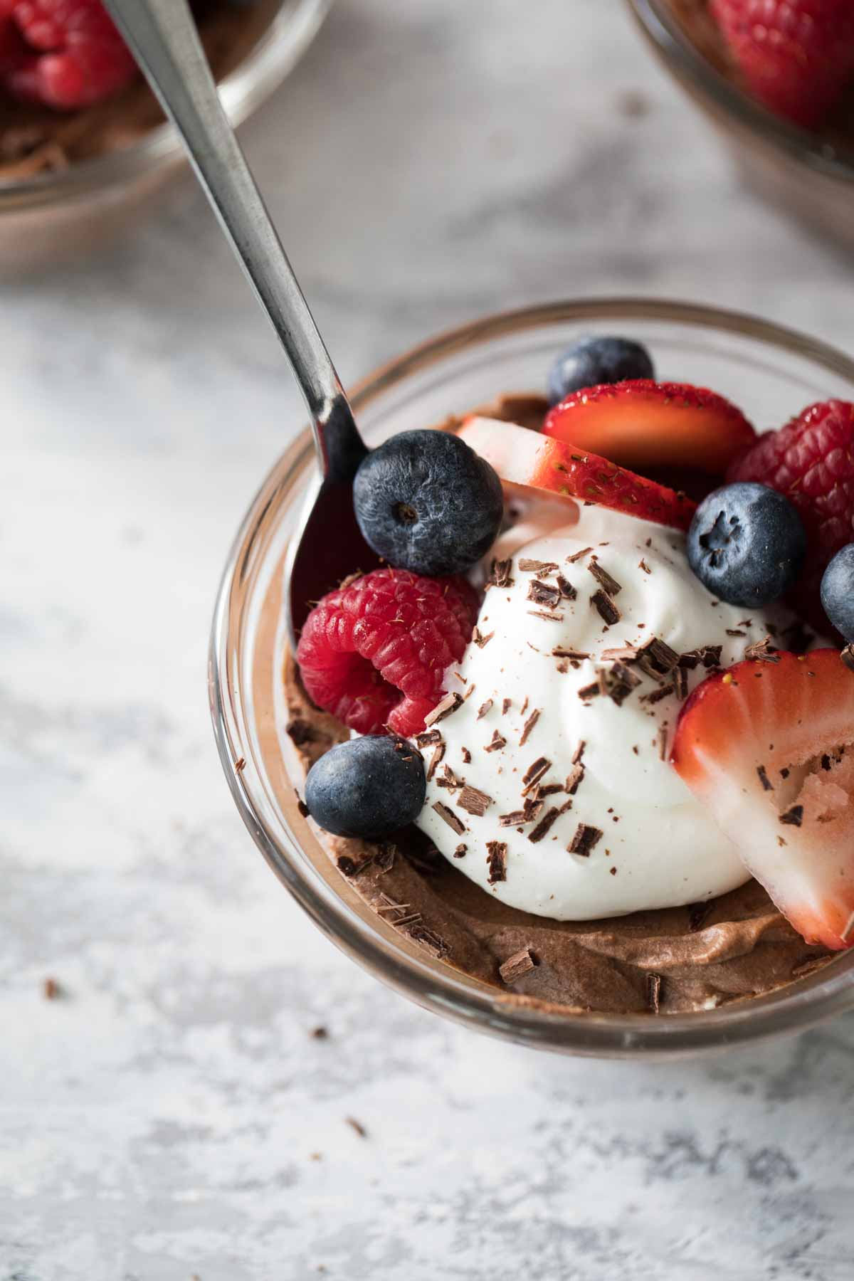 overhead view of chocolate mousse topped with whipped cream and berries