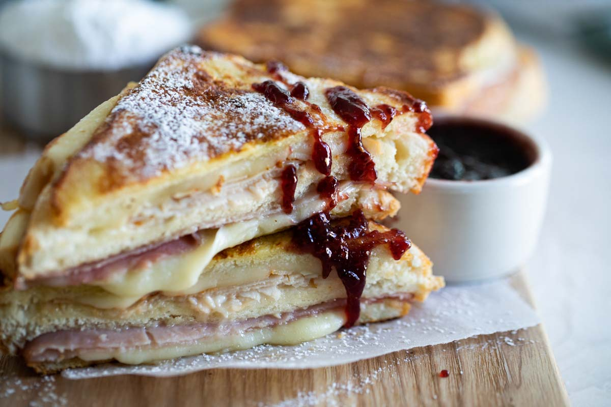 Monte Cristo Sandwich cut in half with jam drizzled on it