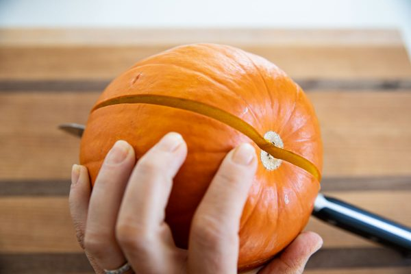Cutting a sugar pumpkin in half