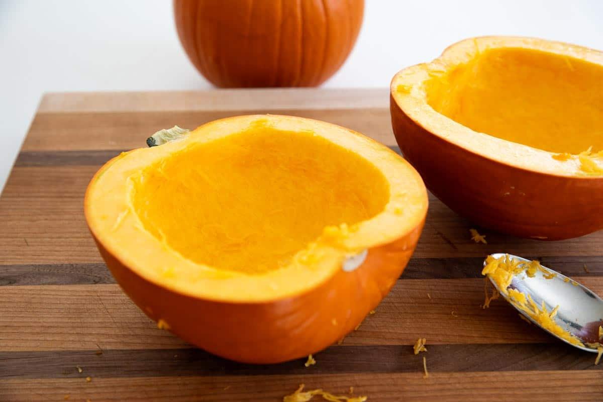 Scooping seeds from pumpkin to make pumpkin puree
