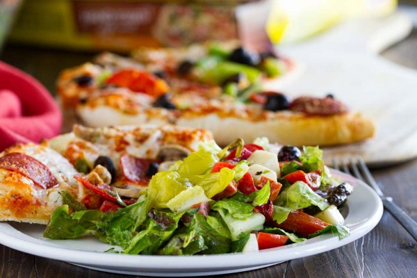 plate with pizza and Antipasto Salad
