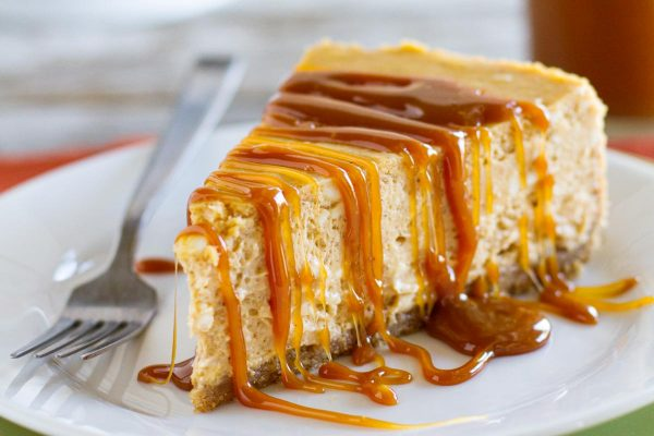 slice of pumpkin cheesecake topped with caramel sauce