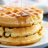 pouring syrup on a stack of waffles