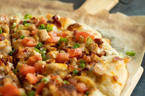 Pizza topped with chicken, bacon, ranch, tomatoes and green onions