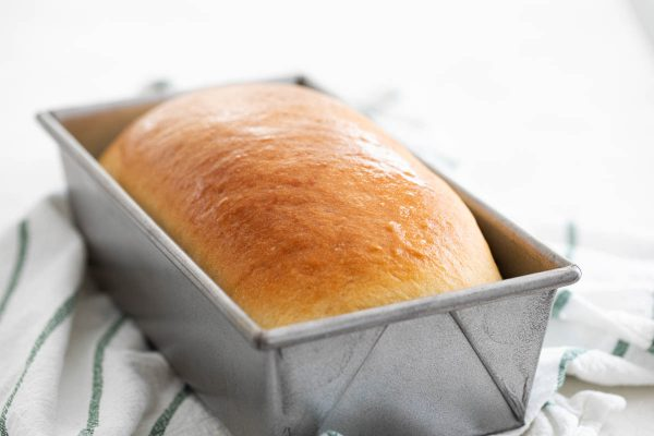 loaf of homemade white bread in a pan