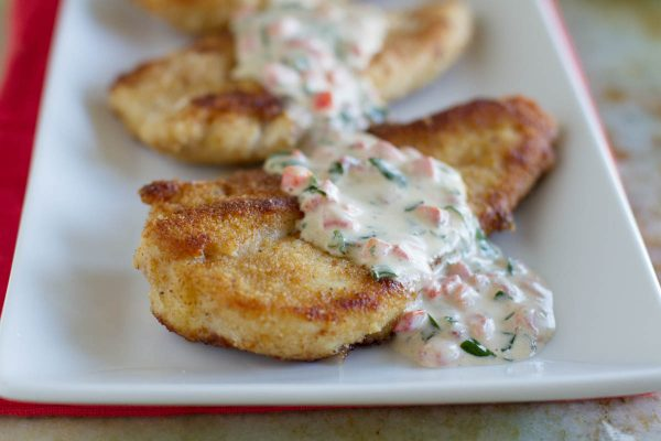 Chicken on a plate with basil cream sauce